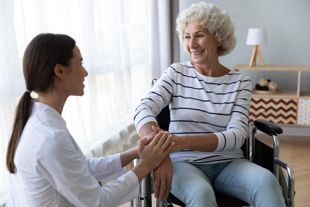 aidante discutant avec une patiente assise dans son fauteuil