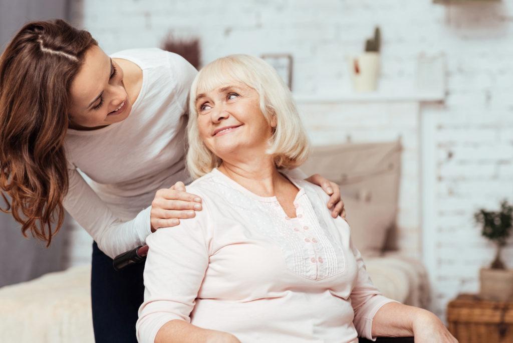 jeune femme tenant les épaules d'une patiente assise